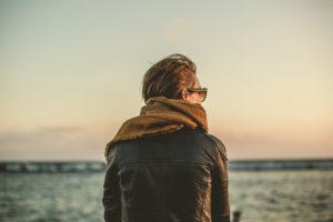 woman wearing scarf sitting next to water at sunset