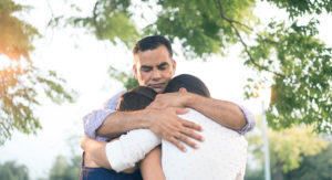 Father embracing wife and daughter.