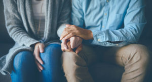 Closeup of two people holding hands and seated.
