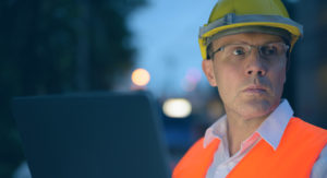 Man in orange vest wearing a yellow hard hat.