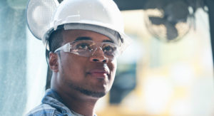 Man wearing PPE: helmet and protective glasses.