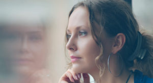 Woman staring out window with reflection in glass.