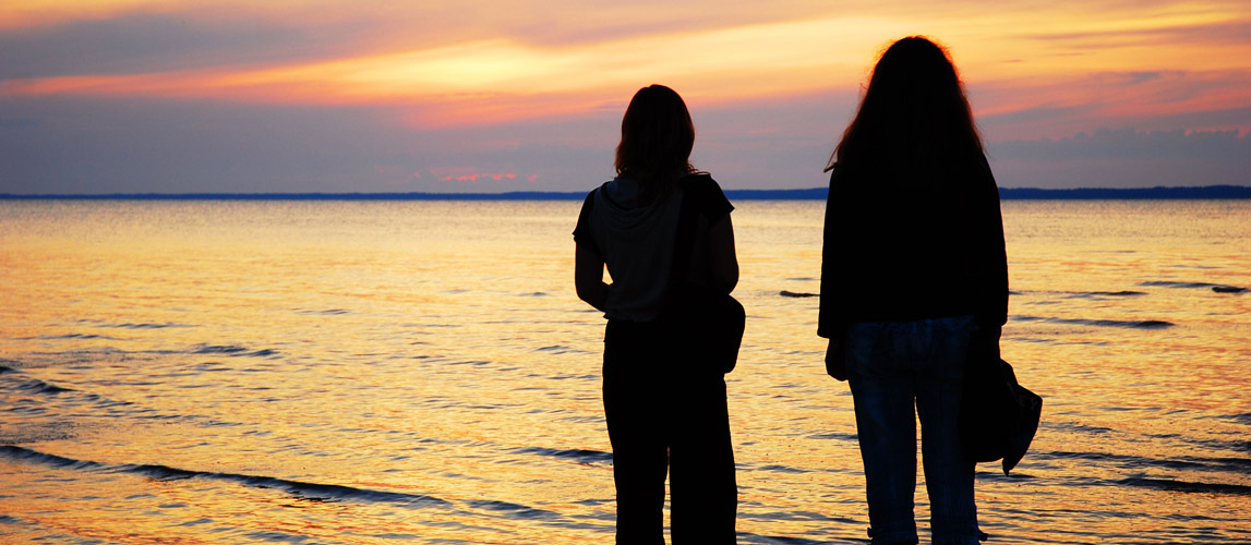 Two women watching sunset across lake.