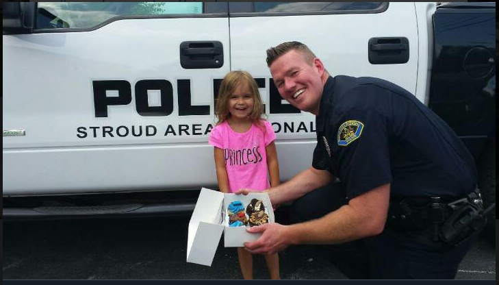 officer giving gift so little girl