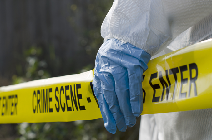 Crime scene tape and biohazard protective glove.