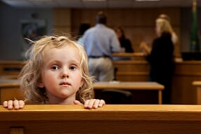 Little blonde girl in court room peering over pew.