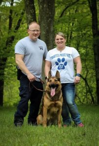 K9 Edo from Marietta Police Department with handlers posing in woods.