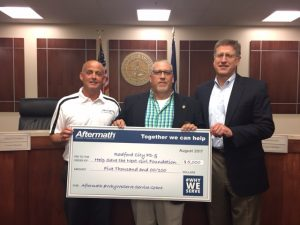 Aftermath presents check to Radford City PD.