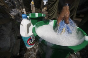 A U.S. Marine with SPMAGTF - Crisis Response - Africa soaks a rag into a bucket of water that contains bleach and soap, in accordance with Centers for Disease Control and Prevention cleaning and decontamination guidelines, before washing equipment as part of the standard procedure prior to leaving the country, while in support of Operation United Assistance in Monrovia, Liberia, Nov. 19, 2014. United Assistance is a Department of Defense operation to provide command and control, logistics, training and engineering support to U.S. Agency for International Development- led efforts to contain the Ebola virus outbreak in West African nations. (U.S. Marine Corps photo by Lance Cpl. Andre Dakis/SP-MAGTF Crisis Response Africa Combat Camera/Released)