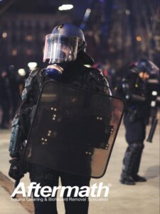 Officer in full ppe and riot gear in street