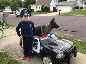 Child in police costume next to toy police car and posing with K9.