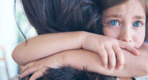Blue eyed child hugging her mom.