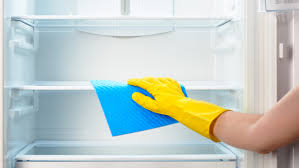 closeup of hand with yellow glove and rag cleaning inside of fridge