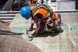 construction worker hunched over hammering a nail into the floorboard