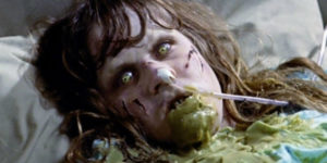 child from film the exorcist laying in bed covered in vomit
