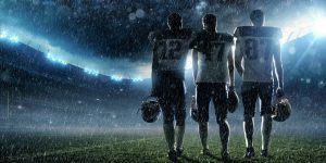 Professional American football players walking during the rain on a professional american football stadium with spotlight. Players are wearing unbranded football cloths.