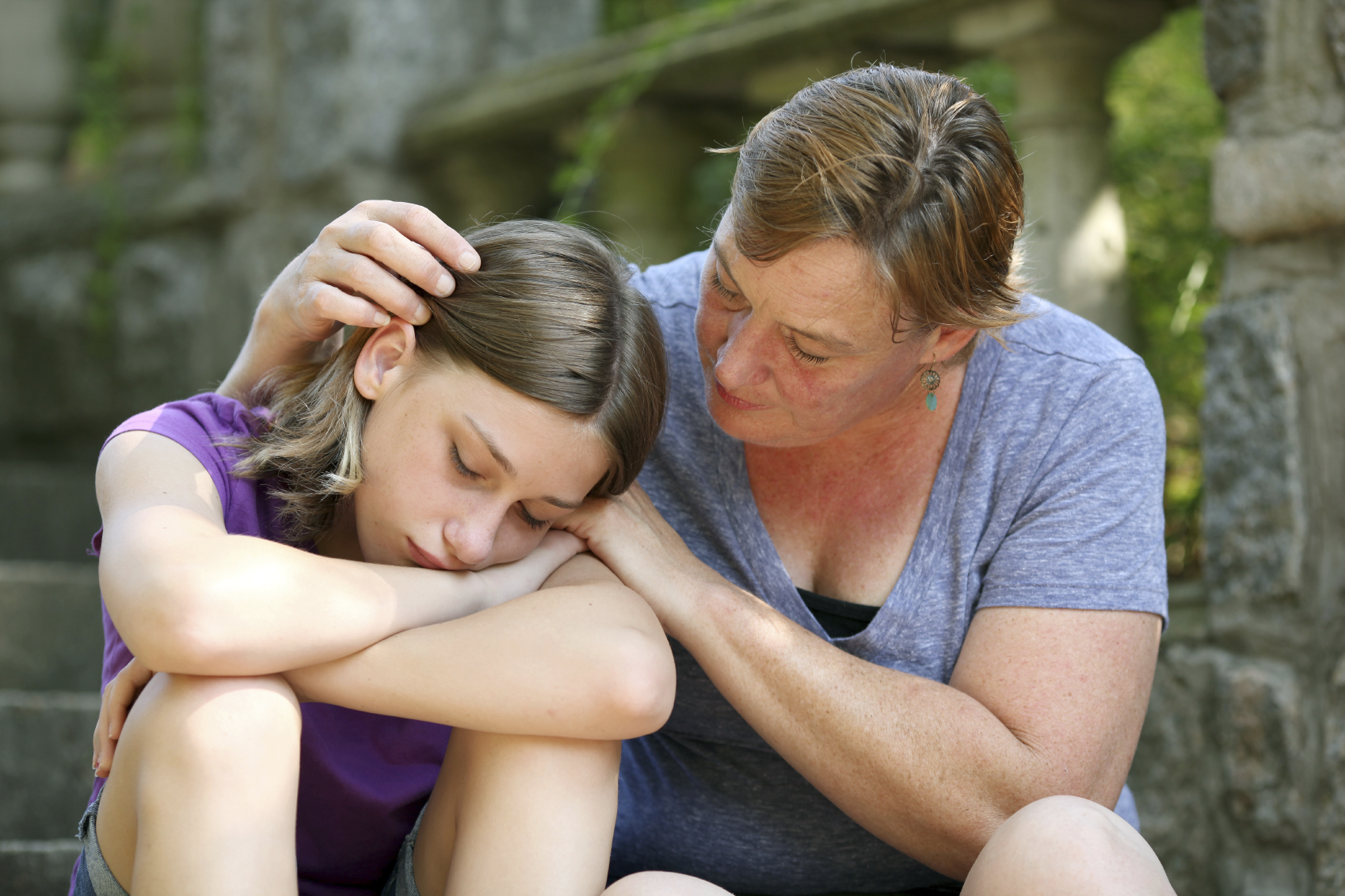 Sad child and mother embracing.