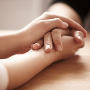 Cropped shot of two people holding hands.