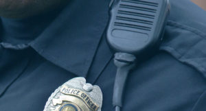 Closeup of police officer badge and radio.