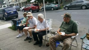 Citizens of Northampton sitting in lawn chairs on sidewalk.