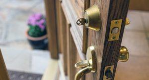 Door ajar with a key in the top lock.