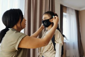 parent helping their child put on a facemask