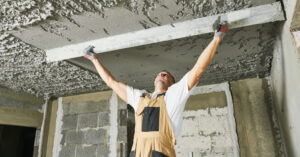 man smoothing plaster on a ceiling