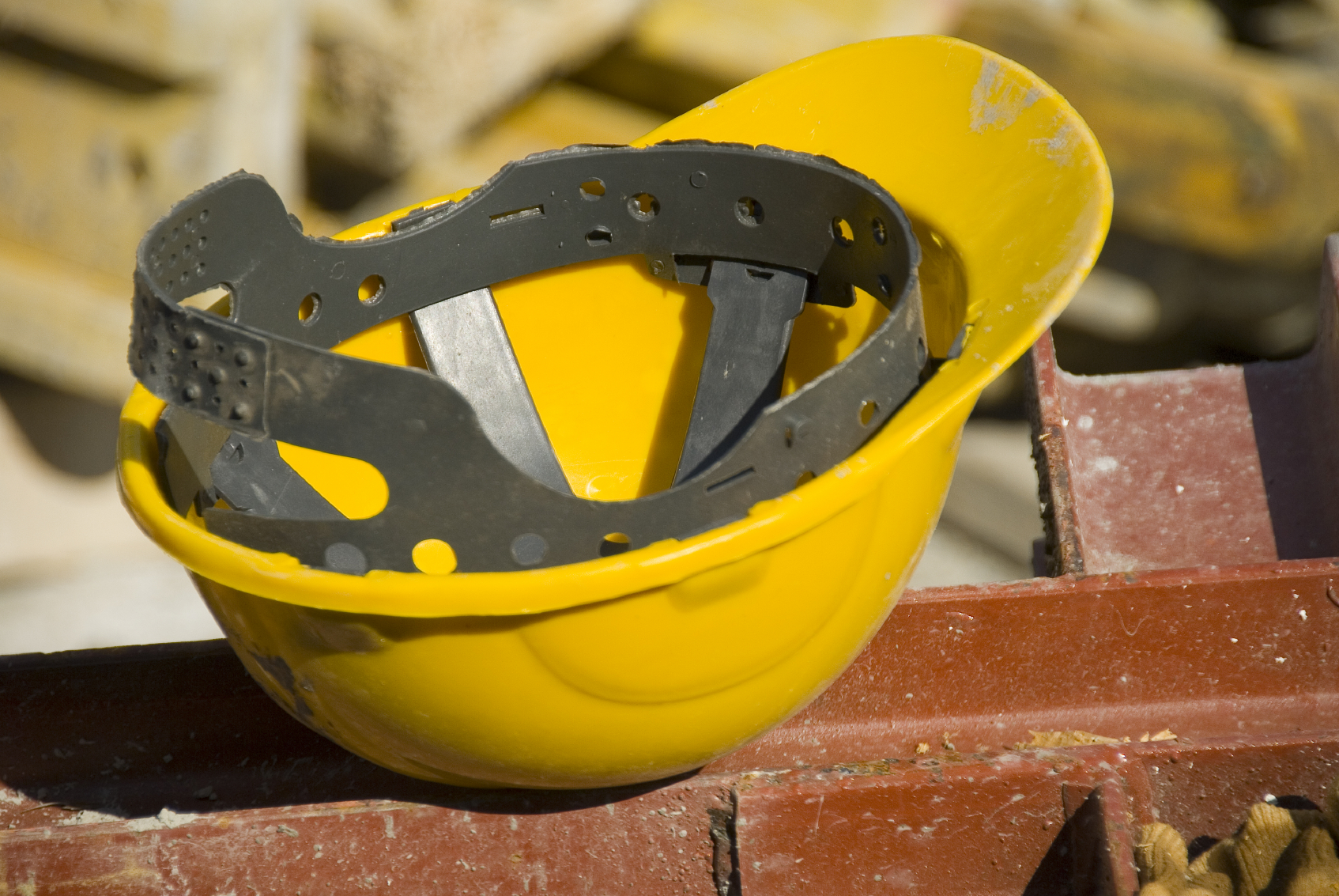 Yellow hard hat sitting on beam after industrial accident.
