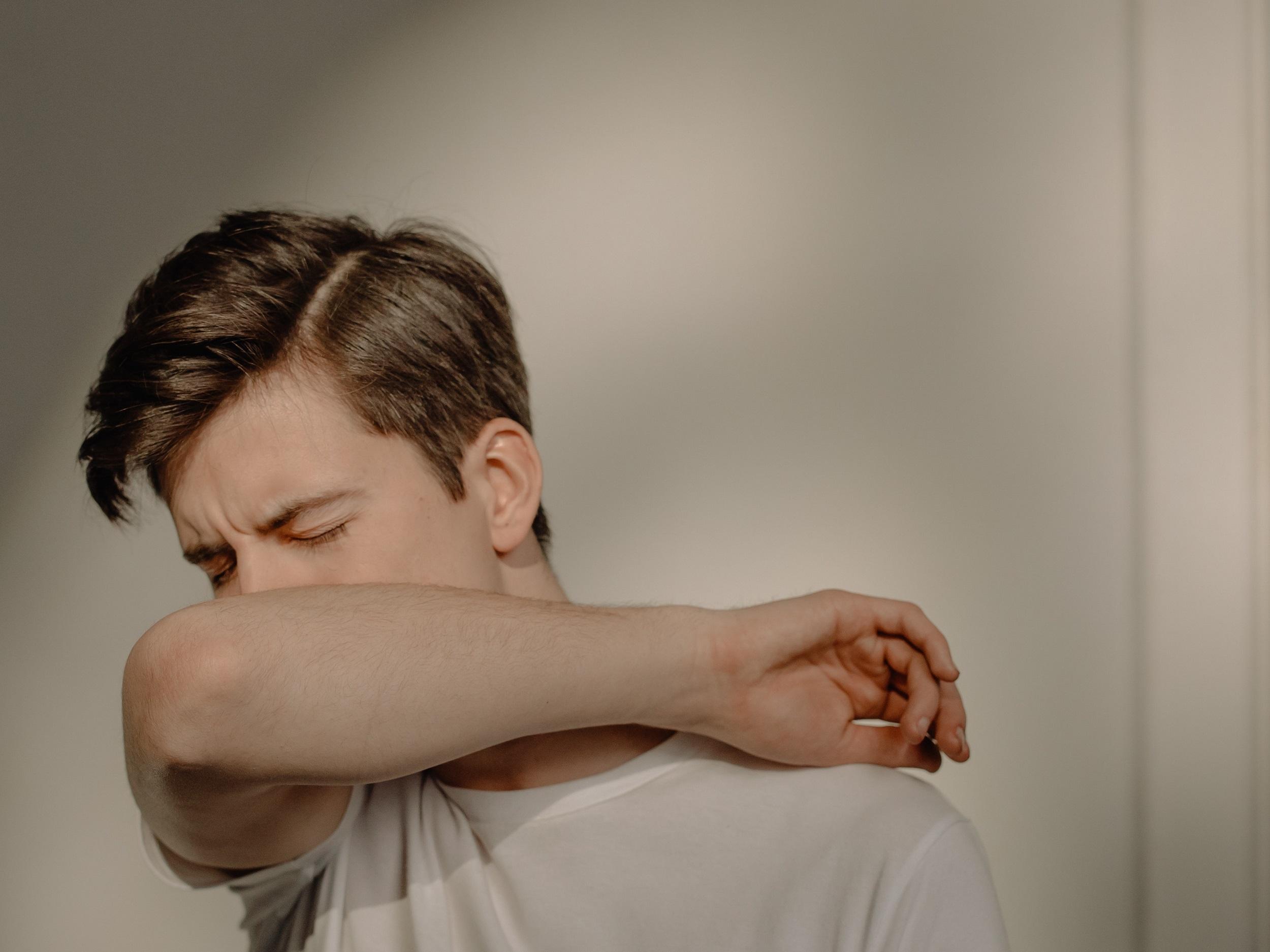 man sneezing into his elbow